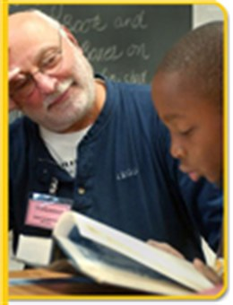 A volunteer helps a student with a reading lesson